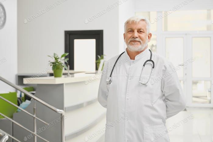 Eldery doctor in lab coat ppsoing near reception