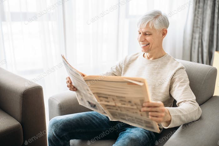 Adult man sitting on couch and reading newspaper