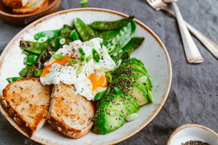 Fried snow peas, avocado, poached eggs are sprinkled chia seeds