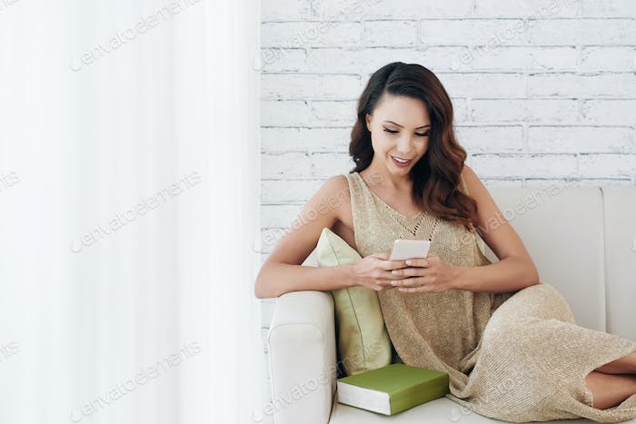 Smiling young woman texting sms to boyfriend