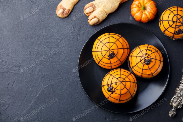 Halloween Cupcakes with Colourful Decoration. Black Slate Background.
