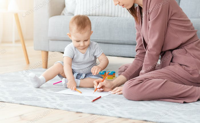Adorable Little Baby Drawing With Pencils On Floor With His Mom