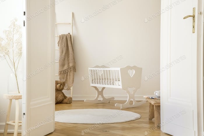 Real photo of white cradle with heart standing in Scandi kid roo