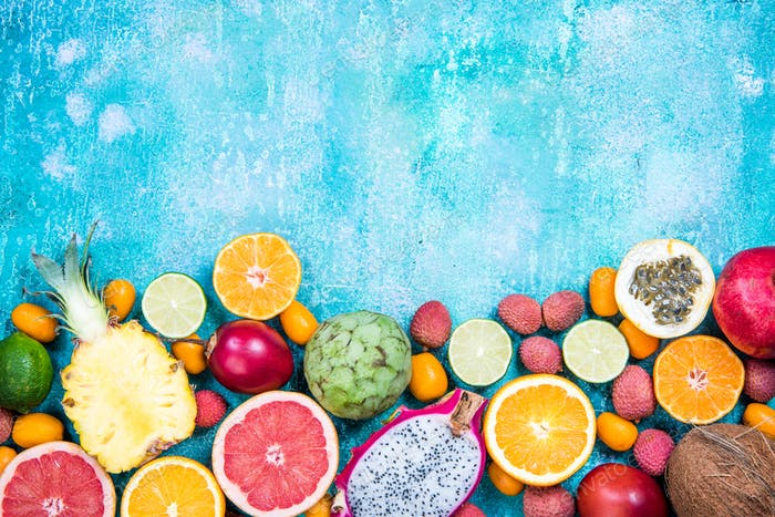 Mixed fresh vibrant exotic fruits, border background