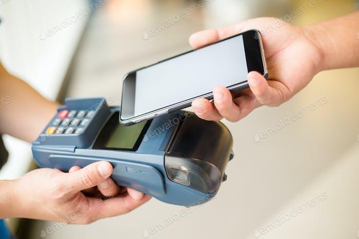 Der Kunde bezahlt die Rechnung mit dem Smartphone