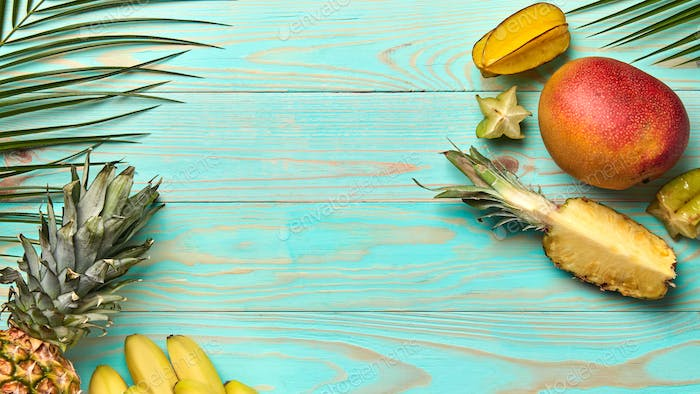 Food frame from different tropical fruits and palm branches on blue wooden background with copy