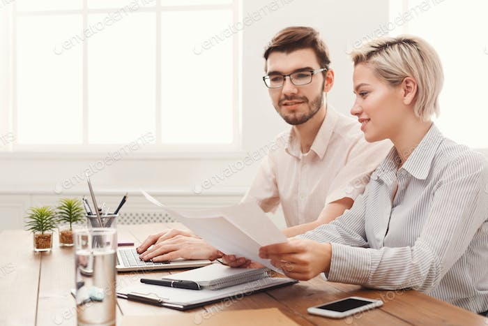 Couple of young colleagues working at modern office