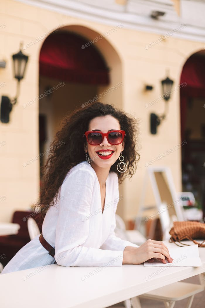 Cheerful lady with dark hair in sunglasses joyfully looking in camera in summer terrace of cafe