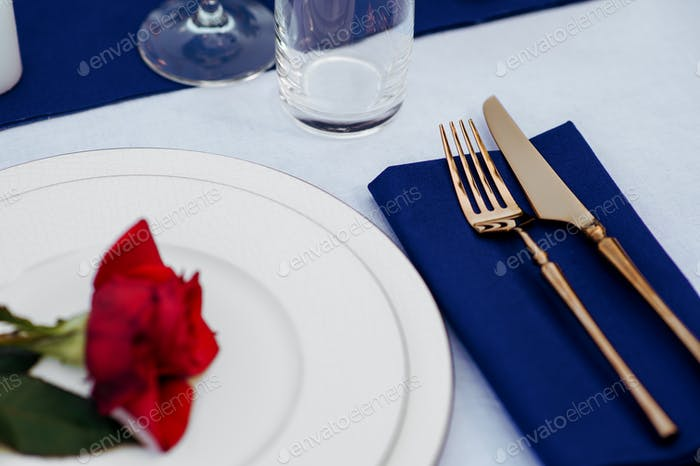 Table setting, silverware and red rose, top view