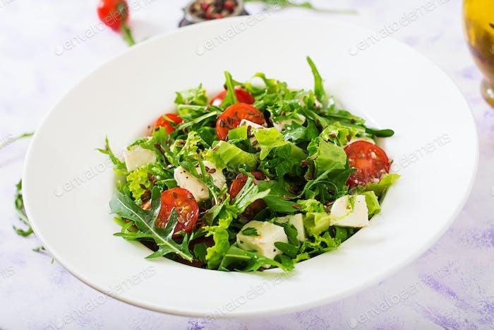 Vitamin Salad of fresh tomatoes, herbs, feta cheese and flax seeds. Dietary menu. Proper nutrition.