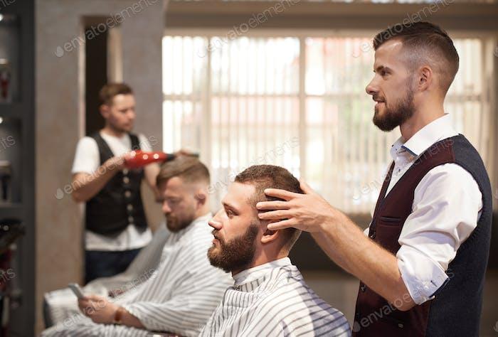 Парикмахерская смотрит на зеркало на волосы клиента перед стрижкой