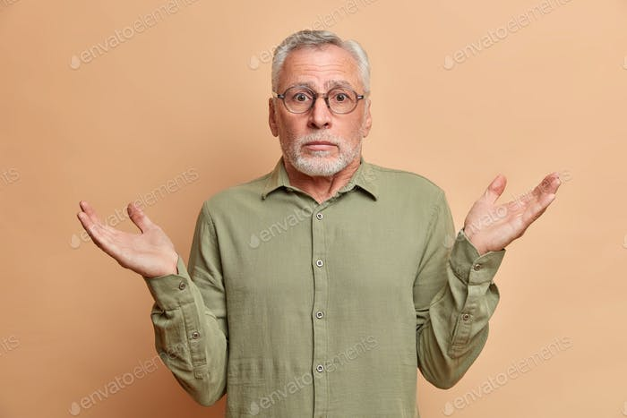Uncertain puzzled grey haired mature bearded man shrugs shoulders with hesitation wears spectacles a