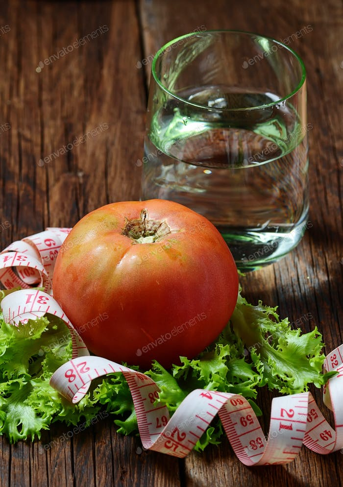 Concept of diet food: vegetable, water and measuring tape