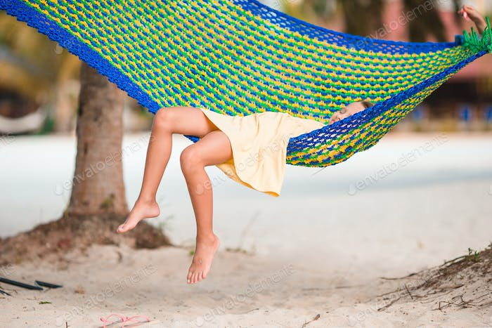 Adorable girl on tropical vacation relaxing in hammock