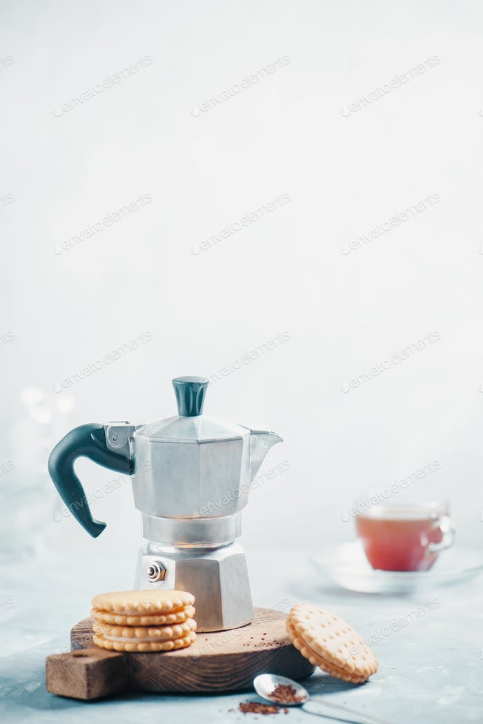 Morning coffee with cookies. Moka pot on a light concrete background with biscuits and espresso cup