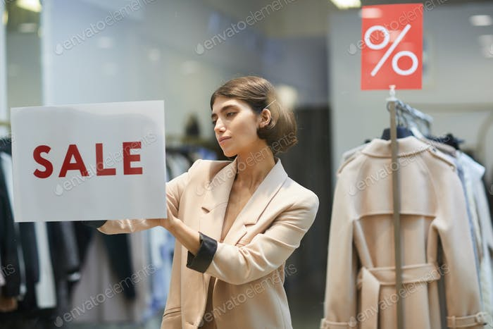Young Woman Hanging Sale Sign in Store