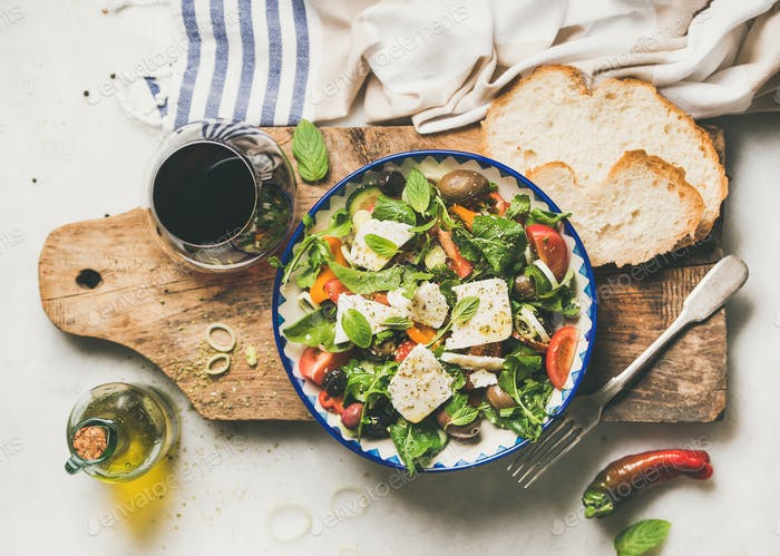 Traditional Greek salad with feta cheese and glass of wine