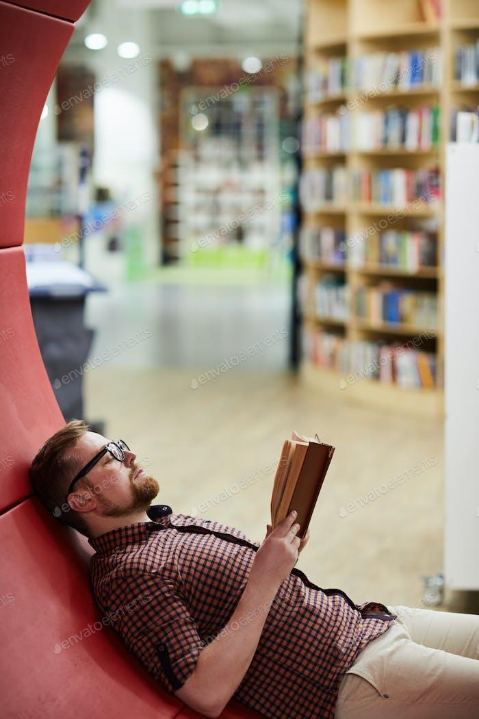 Bärtiger Mann lesen Buch in der Bibliothek