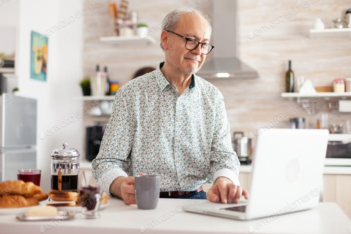 Senior man searching online recipe using laptop