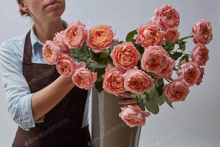 Girl florist in a brown apron with a vase of pink roses on a gray background