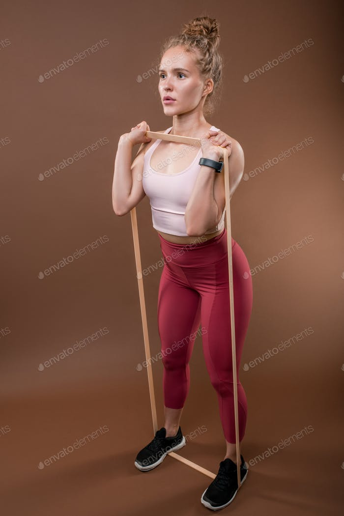 Young sportswoman with curly hair standing on elastic band while exercising
