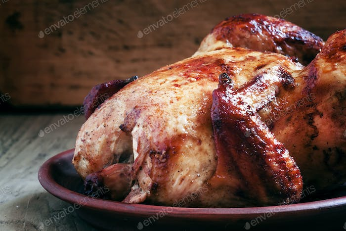 Whole roast chicken with a ruddy crust on a clay dish