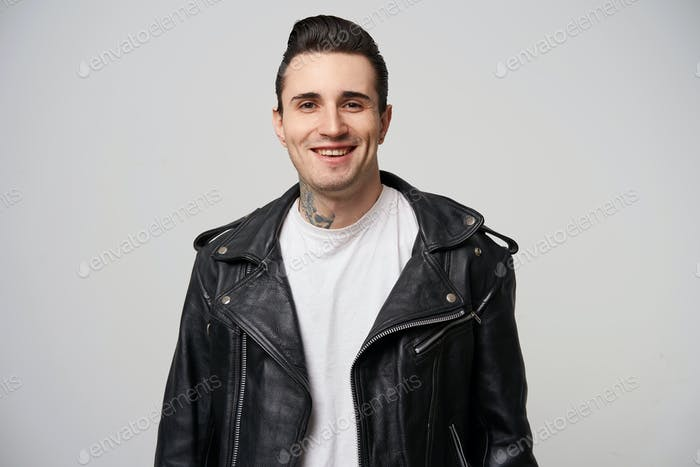 Indoor photo of attractively smiling young rocker man