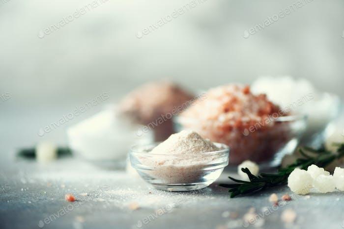Mezcla de diferentes tipos de sal sobre fondo de hormigón gris. Sales marinas, sal negra y rosa del Himalaya
