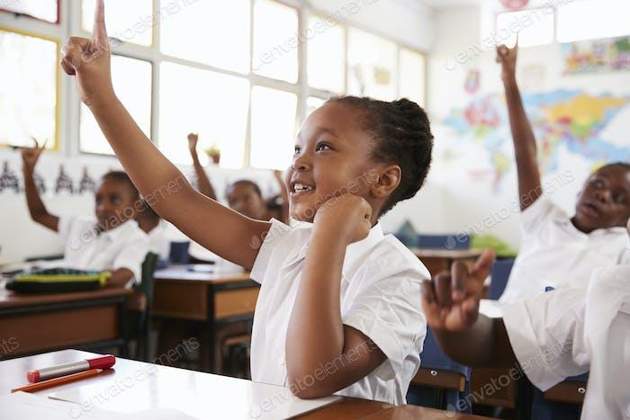 Schulmädchen heben Hand während einer Lektion in der Grundschule