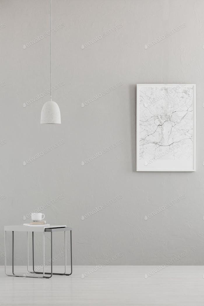 Pendelleuchte über einem modernen Tisch und einem Stadtplan Plakat auf einem gr