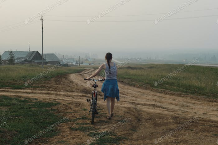 young woman walking with bike, looking on village in evening fog