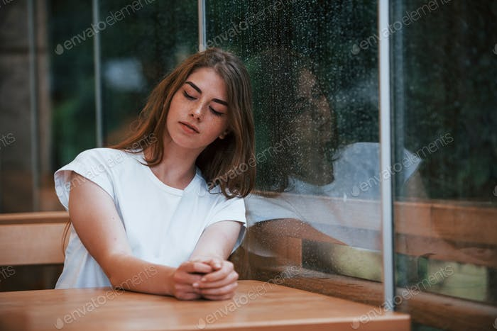 Portrait of young girl that sits in cafe at rainy day. One person only