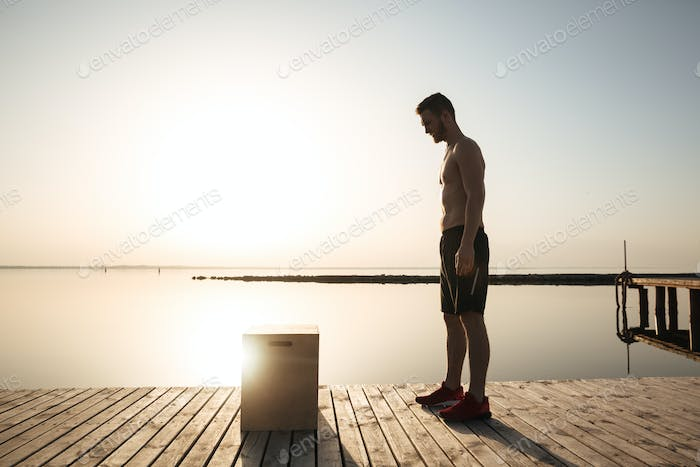 Young fitness man working out in the morning outdoors