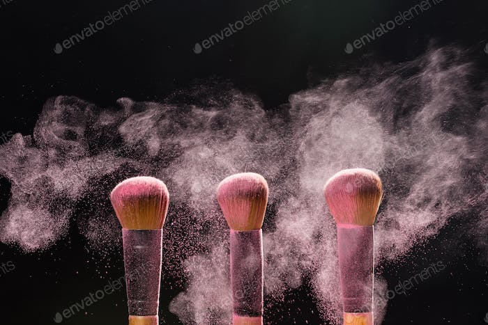 Mineral make up and objects concept - Three make up brushers in pink dust over dark background
