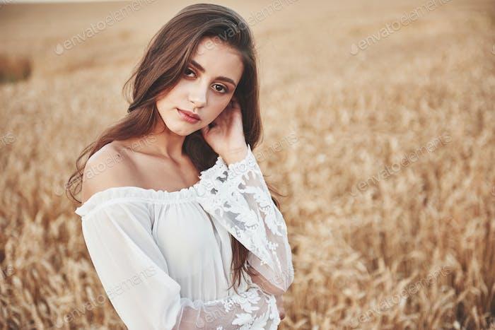 Retrato de una mujer feliz con el pelo largo que está en el campo del trigo