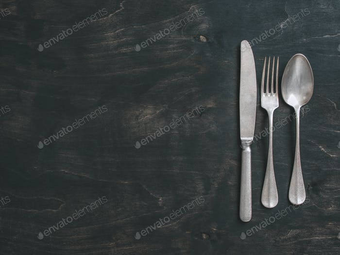 Vintage cutlery on dark background, copy space