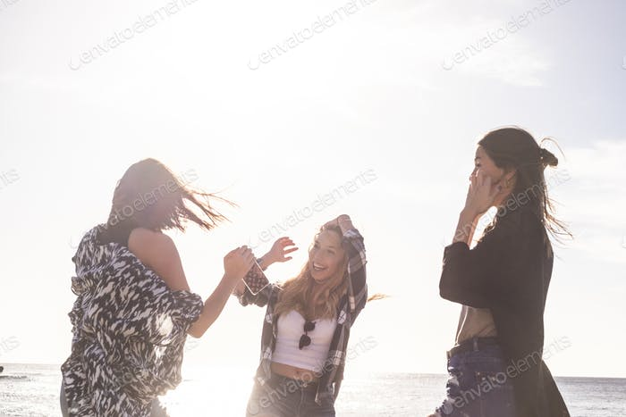 Group of three young woman dance on the beach