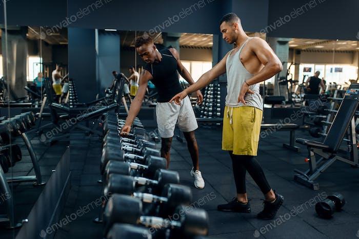 Два спортсмена выбирают тяжелые гантели в тренажерном зале