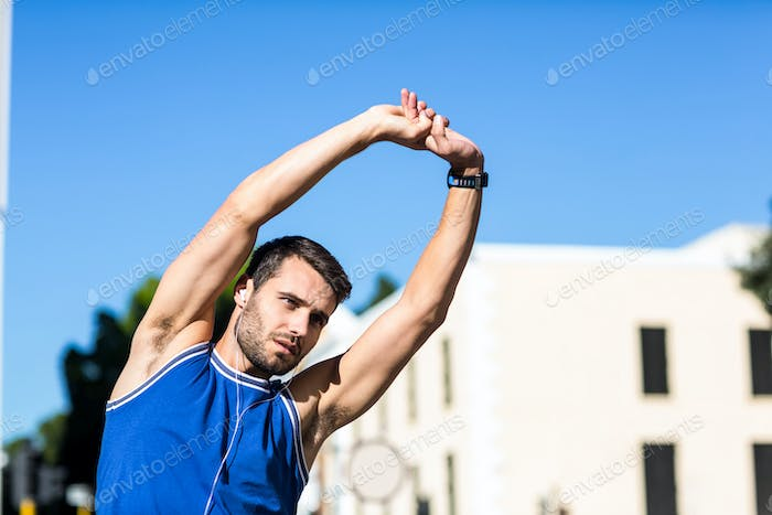An handsome athlete stretching on a sunny day