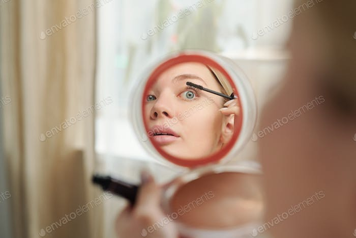 Reflection in mirror of young woman applying black mascara on eyelashes