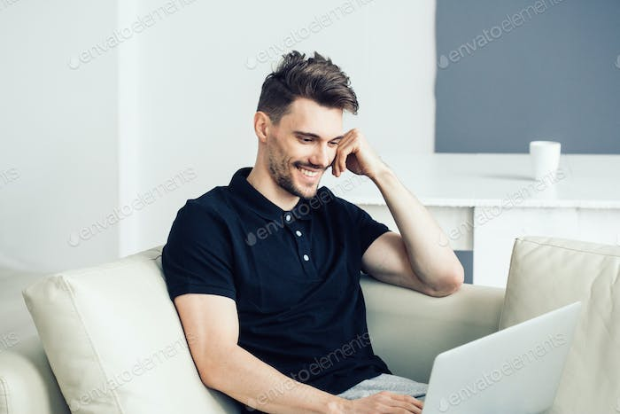 Handsome man with laptop home. Male portrait freelancer working home with computer