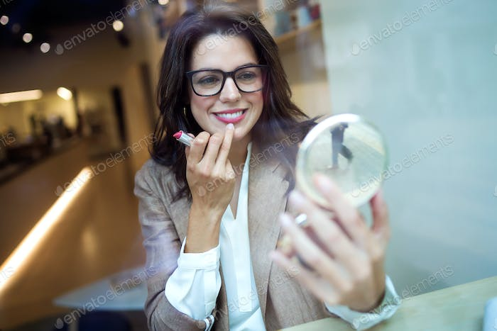 Beautiful young businesswoman looking in the mirror and applying lipstick in the coffe shop.