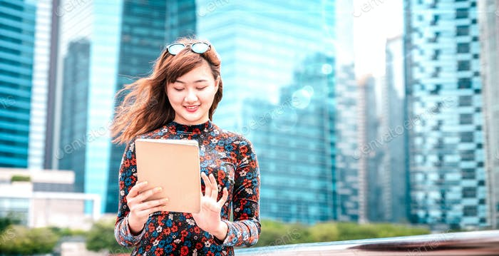 Young asian woman using electronic device at modern city