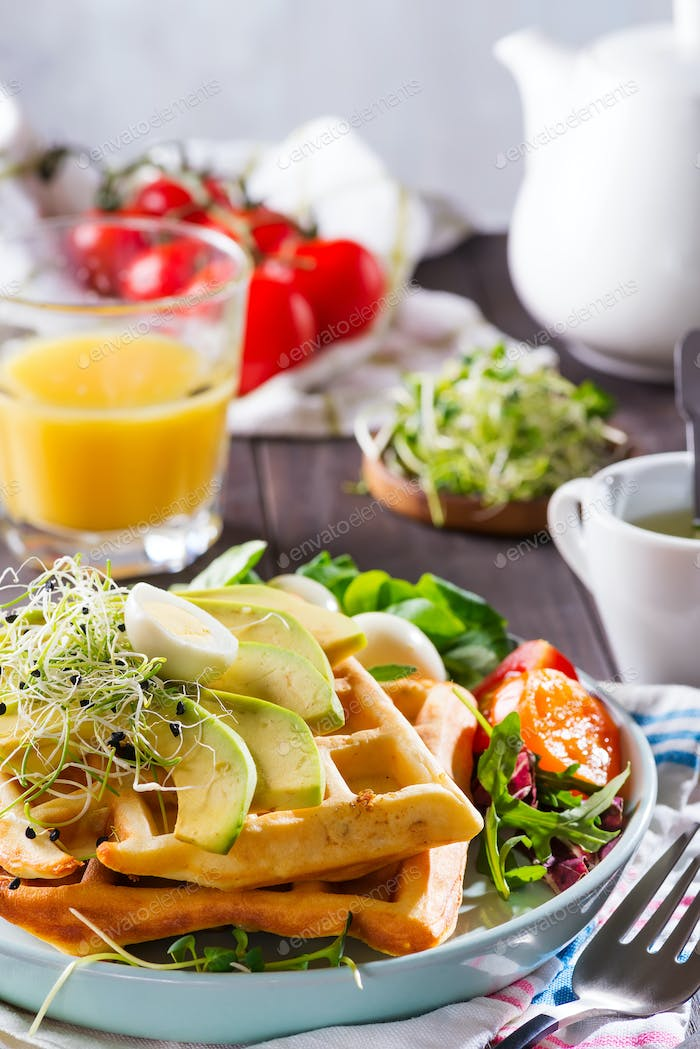 Belgian Waffles with avocado, eggs, micro green and tomatoes with orange juice on wooden table
