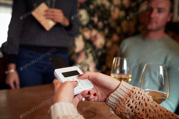 Close Up Of Customer In Restaurant PIN-Nummer in Kreditkartenterminal eingeben