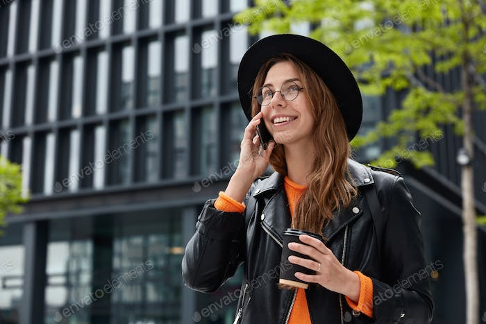 Joyful European woman with happy facial expression, has telephone conversation in roaming, drinks co
