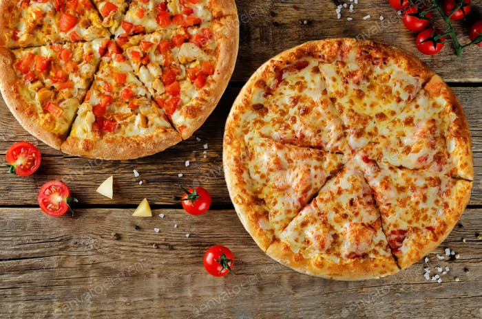 Pizza with cheese, tomato sauce and fresh tomatoes on a wood background