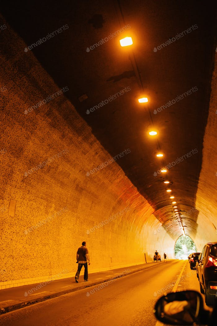 view through tunnel with car and walking people and warm lights in Budapest city