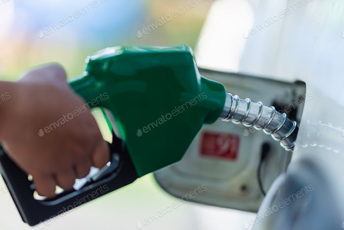 Handle pumping gasoline fuel nozzle to refuel. Vehicle fueling facility at petrol station