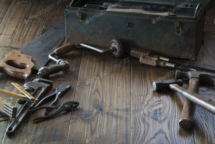 Antique tools and toolbox on dark wood surface